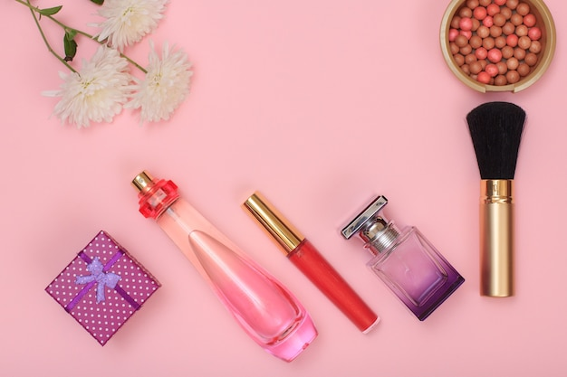 Pudełko prezentowe, butelki z perfumami, szminką, pędzlem i pudrem na różowym tle. kosmetyki i akcesoria dla kobiet. widok z góry.