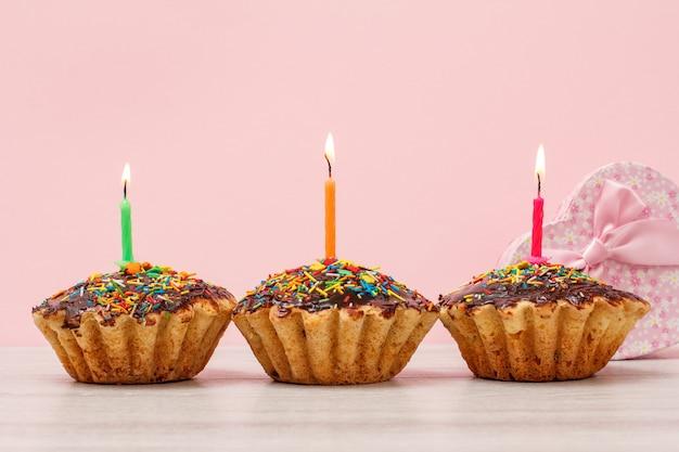 Pudełko prezentowe i smaczne urodzinowe babeczki z polewą czekoladową i karmelem, ozdobione płonącymi świątecznymi świeczkami na drewnianym i różowym tle. koncepcja wszystkiego najlepszego.