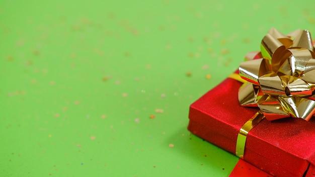 Pudełko prezentowe lub prezentowe i konfetti na czerwonym i zielonym tle. płaska kompozycja świeckich na boże narodzenie