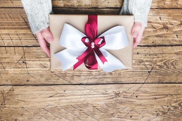 Pudełko prezentowe lub prezentowe z dużą kokardą w rękach kobiety w swetrze. kompozycja płasko świecka na boże narodzenie, urodziny, dzień matki lub ślub.