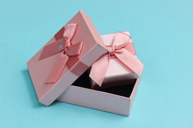 Pudełko prezentowe na niebieskiej powierzchni.