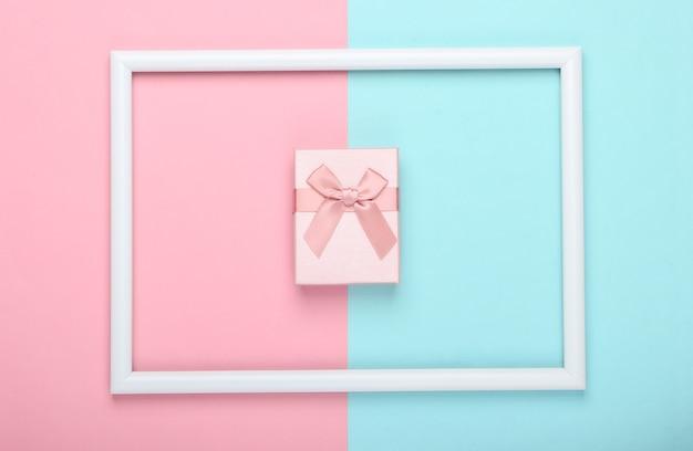 Pudełko prezentowe na różowo-niebieskiej pastelowej powierzchni z białą ramką