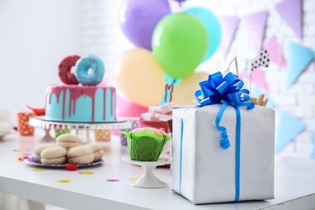 Pudełko prezentowe na stole ze słodyczami przygotowane na przyjęcie urodzinowe