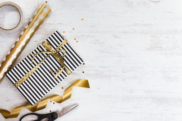 Pudełko prezentowe owinięte czarno-białym pasiastym papierem ze złotą kokardką i materiałami do pakowania