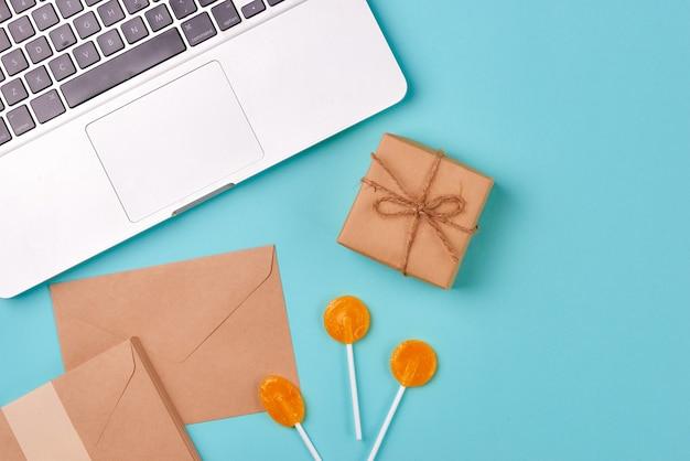 Pudełko prezentowe, rzeczy urodzinowe i laptop na niebieskim tle