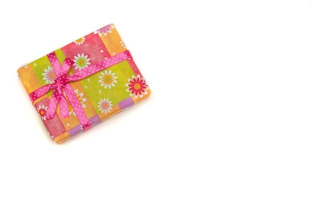 Pudełko prezentowe w jasnym opakowaniu na białym tle kopia przestrzeń widok z góry różowa wstążka w kropki, proces pakowania prezentów, święto dziękczynienia, wakacje, urodziny, prezent dla dziewczyny, dziecka, prezent