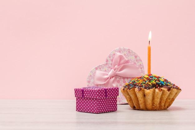Pudełko prezentowe w kształcie serca i małego, smaczna urodzinowa babeczka z polewą czekoladową i karmelem, ozdobiona płonącą świąteczną świeczką na drewnianym i różowym tle. koncepcja wszystkiego najlepszego.