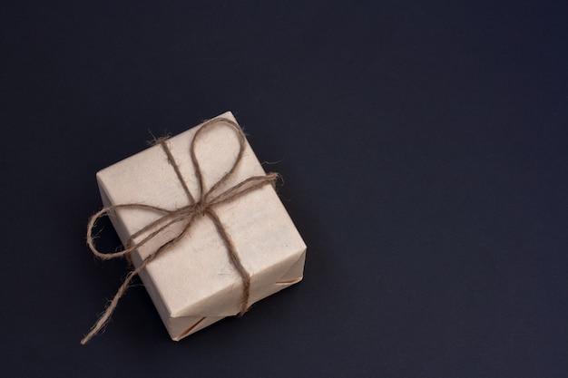 Pudełko prezentowe wykonane z szarego papieru rzemieślniczego przewiązanego konopną liną z kokardką. ciemnoniebieskie tło. skopiuj miejsce.