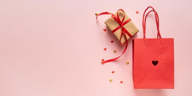 Pudełko prezentowe z czerwoną wstążką, papierową torbą i czerwonymi sercami