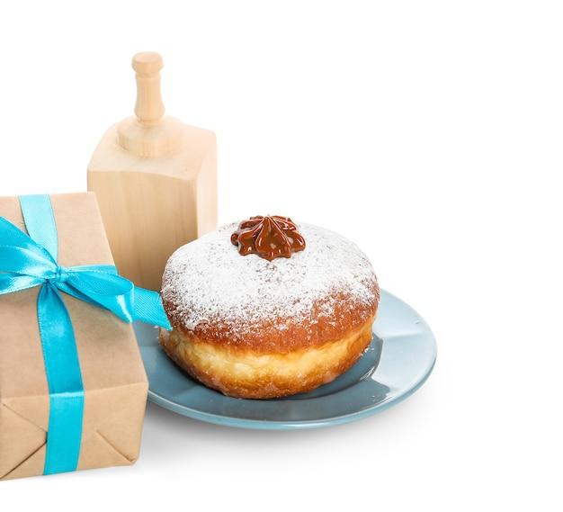 Pudełko prezentowe z drejlem i pączkiem na chanukę na białej powierzchni