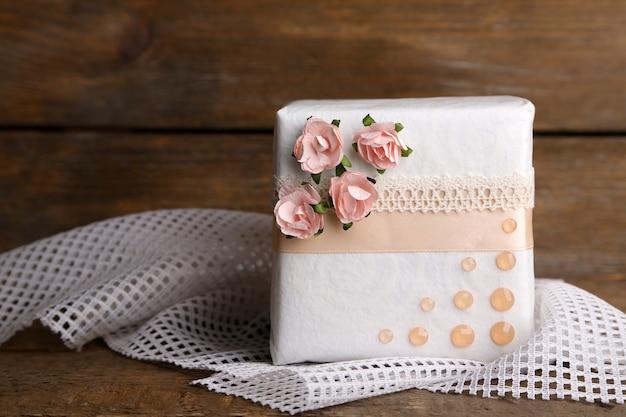 Pudełko prezentowe z kolorową wstążką i papierowymi kwiatami na drewnianym tle
