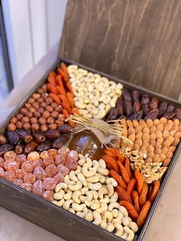 Pudełko prezentowe z orzechami, bakaliami i miodem. drewniane pudełko z jedzeniem