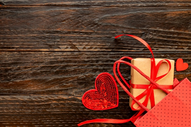 Pudełko prezentowe z papieru ozdobnego z kokardą z czerwonej wstążki, papierową torbą i czerwonymi sercami. świąteczna koncepcja na walentynki, dzień matki lub urodziny.
