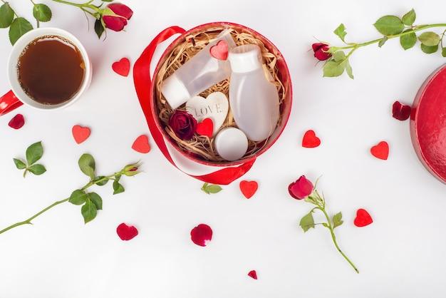 Pudełko prezentowe z produktami kosmetycznymi, ozdobne serduszka, róże.