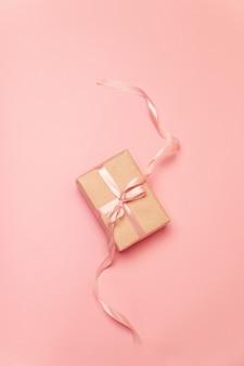 Pudełko prezentowe z różową pastelową wstążką na różowym płótnie
