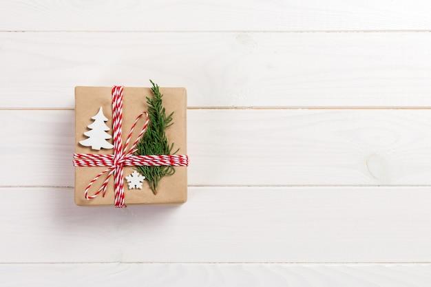 Pudełko prezentowe zawinięte w papier z recyklingu, ze wstążką, z wystrojem świątecznym.
