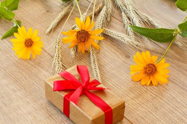 Pudełko prezentowe, żółte kwiaty i kłosy pszenicy na drewnianych deskach. widok z góry.
