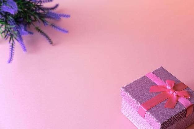 Pudełko przewiązane wstążką z bukietem fioletowych kwiatów
