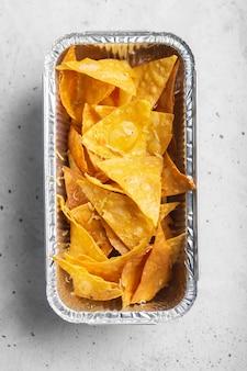 Pudełko pysznych chipsów kukurydzianych tortilla z sosem serowym. meksykańskie jedzenie