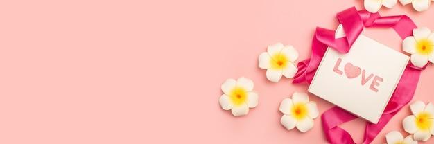 Pudełko, różowa wstążka i kwiaty na pastelowo różowej powierzchni
