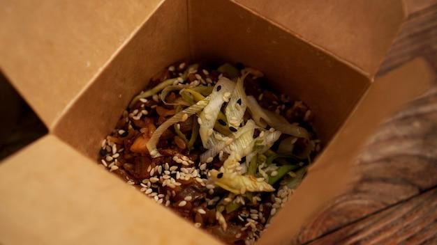 Pudełko smażonego ryżu z warzywami i mięsem. smaczna mieszanka. koncepcja chińskiego fast foodu.