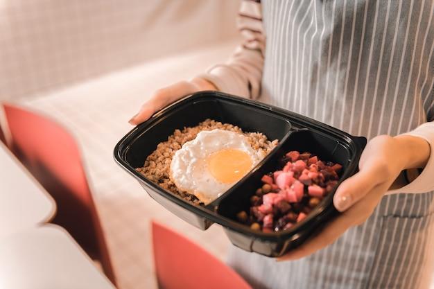 Pudełko śniadaniowe. młoda pracowita kelnerka w pasiastym fartuchu przynosząca klientowi pudełko na lunch