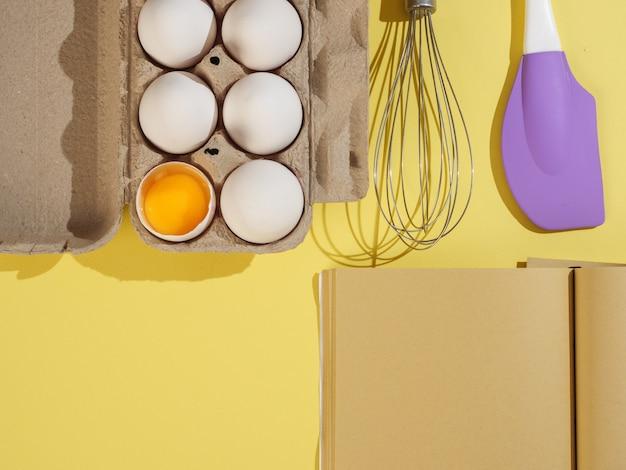 Pudełko tekturowe z białymi jajami kurzymi, książeczką z papieru kraftowego i narzędziami cukierniczymi. widok z góry.
