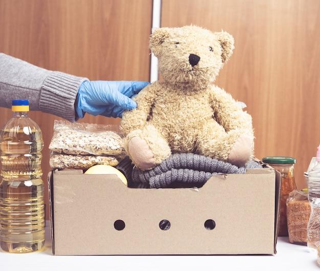 Pudełko tekturowe z jedzeniem i rzeczami potrzebującymi, koncepcja pomocy