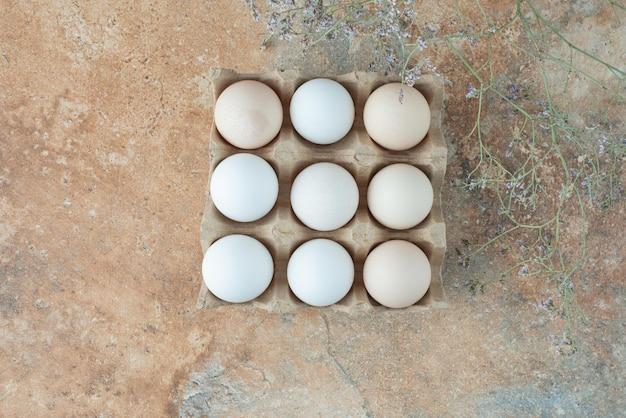 Pudełko tekturowe ze świeżymi białymi jajkami kurczaka na marmurowym stole.