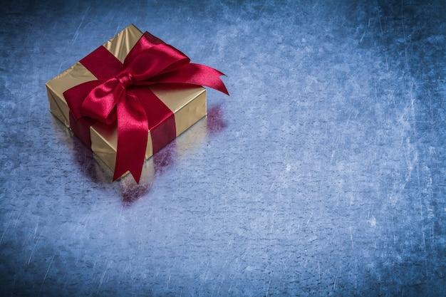 Pudełko upominkowe owinięte błyszczącym złotym papierem na metalowej powierzchni.