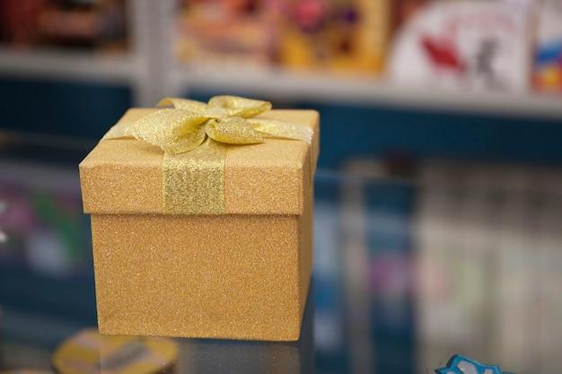 Pudełko upominkowe w kolorze złotym ze złotą kokardką stoi na powierzchni