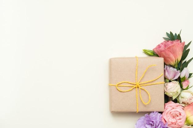 Pudełko upominkowe z papieru rzemieślniczego i różne kwiaty. widok z góry