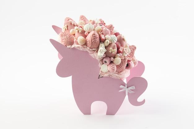 Pudełko w kształcie jednorożca wypełnione różowymi słodyczami, truskawki w czekoladzie na białym tle