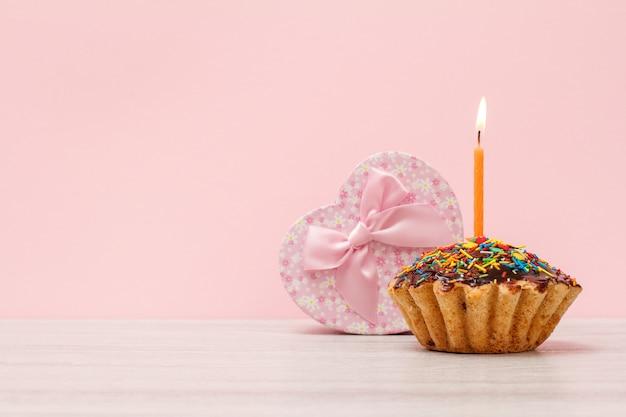 Pudełko w kształcie serca i smaczne urodzinowe muffinki z polewą czekoladową i karmelem, ozdobione płonącą świąteczną świeczką na drewnianym i różowym tle z kopią miejsca. koncepcja wszystkiego najlepszego.