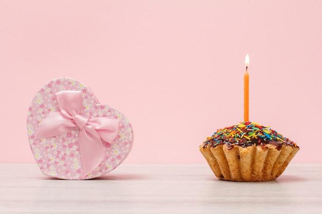 Pudełko w kształcie serca i smacznej urodzinowej muffinki z polewą czekoladową i karmelem, ozdobione płonącą świąteczną świeczką na drewnianym i różowym tle.