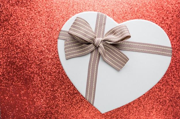 Pudełko w kształcie serca na błyszczące świąteczne lampki rozmazane abstrakcyjne czerwone tło