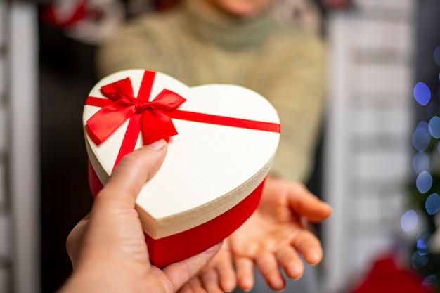 Pudełko w kształcie serca w dłoni na tle choinki