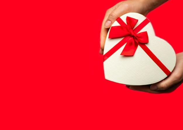 Pudełko w kształcie serca w ręce na czerwonym tle