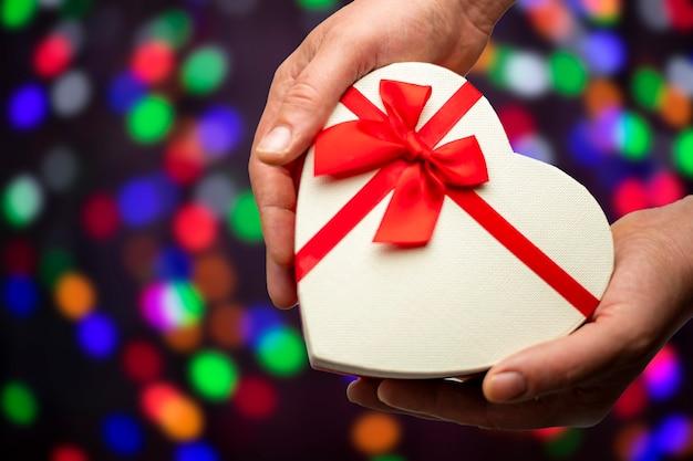 Pudełko w kształcie serca w ręce na wielokolorowym tle