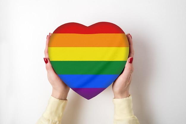 Pudełko w kształcie serca w rękach kobiet. koncepcja tolerancji lgbt.