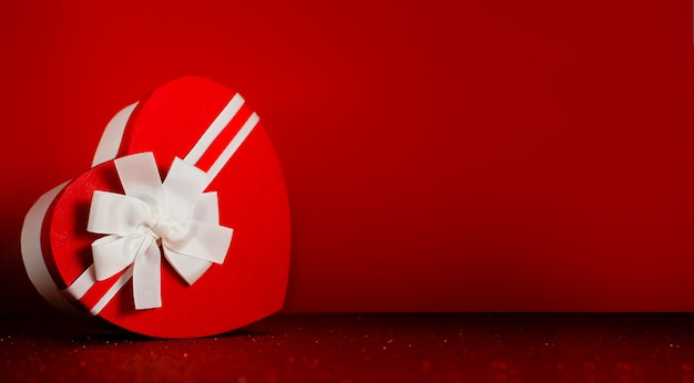 Pudełko w kształcie serca z błyszczącym czerwonym tłem wstążki. koncepcja świętego walentego i zaangażowania.