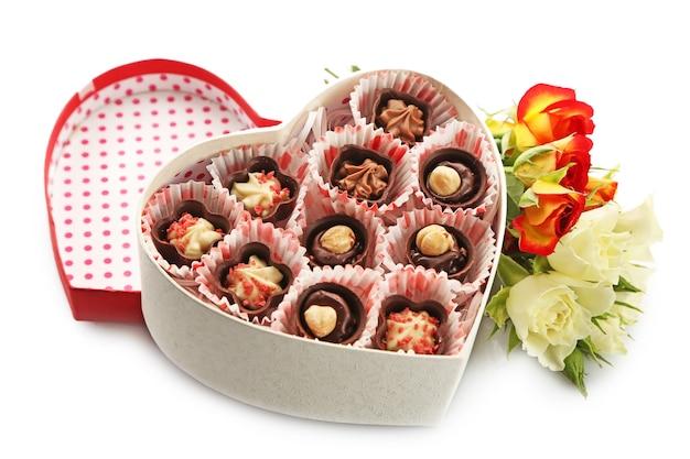 Pudełko w kształcie serca z cukierkami i kwiatami na białym tle