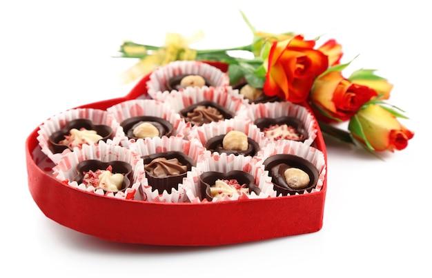 Pudełko w kształcie serca z cukierkami i kwiatami, na białym tle