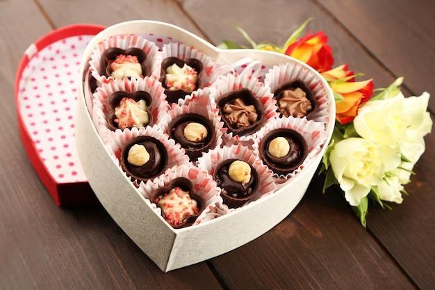 Pudełko w kształcie serca z cukierkami i kwiatami na drewnianym tle, zbliżenie