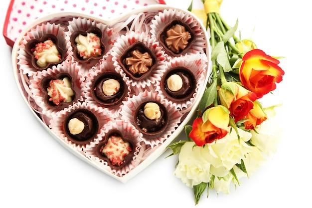 Pudełko w kształcie serca z cukierkami i kwiatami, z bliska