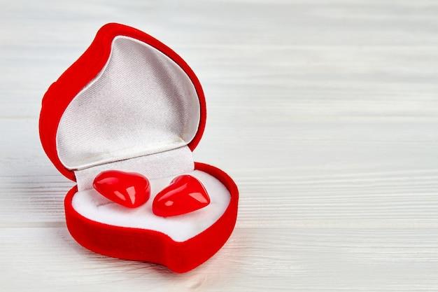 Pudełko w kształcie serca z czerwonymi kolczykami. pudełko na prezent walentynki z dwoma czerwonymi akcesoriami w kształcie serca i miejscem na kopię.