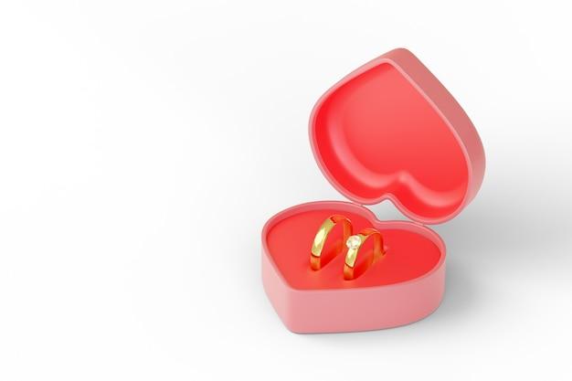 Pudełko w kształcie serca z dwoma obrączkami na białym tle.