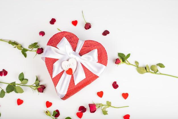 Pudełko w kształcie serca z kokardą na białym tle z różami i sercem.