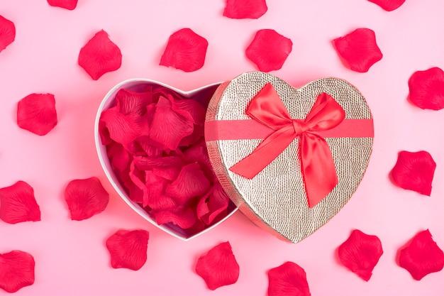 Pudełko w kształcie serca z płatkami róż wewnątrz na różowym tle happy valentine's day concept
