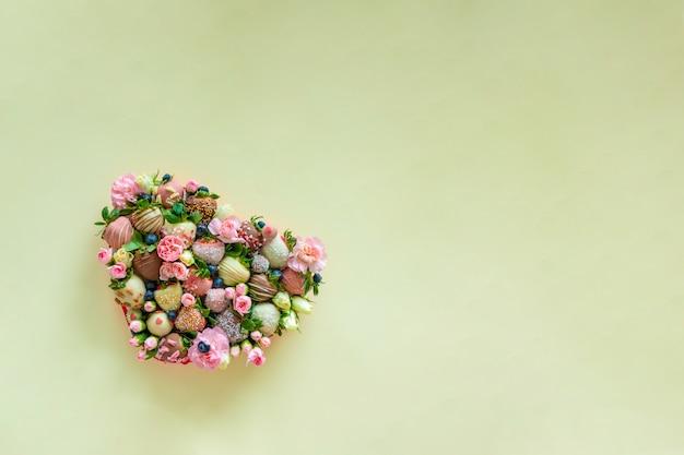Pudełko w kształcie serca z ręcznie truskawką w czekoladzie i kwiaty jako prezent na walentynki na zielonym tle z bezpłatną przestrzenią na tekst